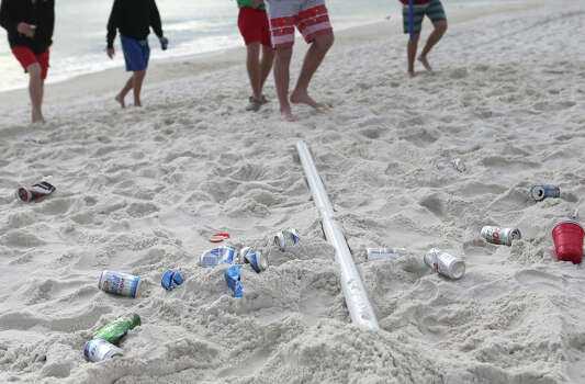 Discarded beer cans and other trash begins to fill the sandy white beaches during the first week of Spring Break on Friday, March 6, 2015, in Panama City Beach, Fla. Photo: Heather Leiphart, AP / The Panama City News Herald