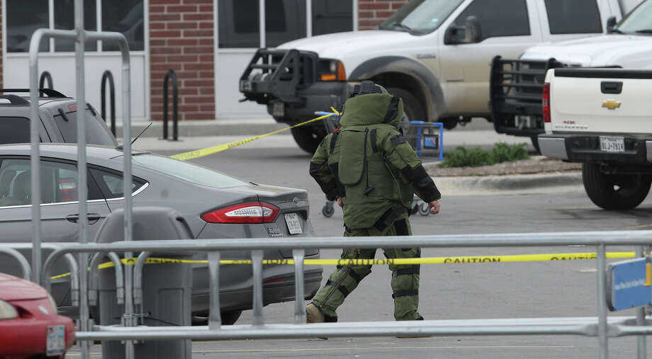 San Antonio police investigate at the scene of a suspicious device at a Walmart parking lot Monday March 16, 2015 at Southwest Loop 410 and Ray Ellison. Police at the scene said a section of PVC pipe was found under a car and was destroyed. Shoppers at the store were advised to remain inside the store until the parking lot was found to be safe.The scene took place about 11:00a.m. . Photo: John Davenport, San Antonio Express-News / ©San Antonio Express-News/John Davenport