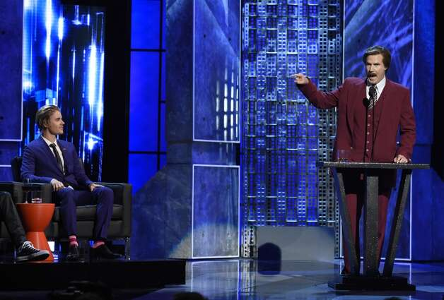 "Will Ferrell, right, appears in character as Ron Burgundy from ""The Anchorman"" films, as Justin Bieber looks on at the Comedy Central Roast of Justin Bieber at Sony Pictures Studios on Saturday, March 14, 2015, in Culver City, Calif. Looking on from left is Justin Bieber. Photo: Chris Pizzello, Associated Press"
