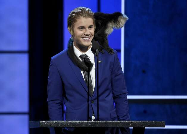 A monkey rests on Justin Bieber's shoulder as he speaks at the Comedy Central Roast of Justin Bieber at Sony Pictures Studios on Saturday, March 14, 2015, in Culver City, Calif. Photo: Chris Pizzello, Associated Press