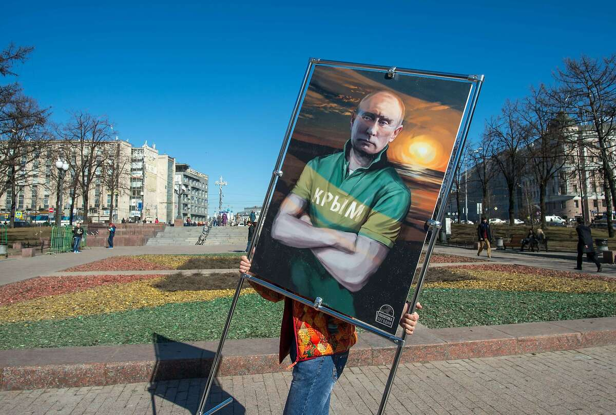 A man carries a picture depicting Russia's President Vladimir Putin in a T-shirt with an inscription reading: