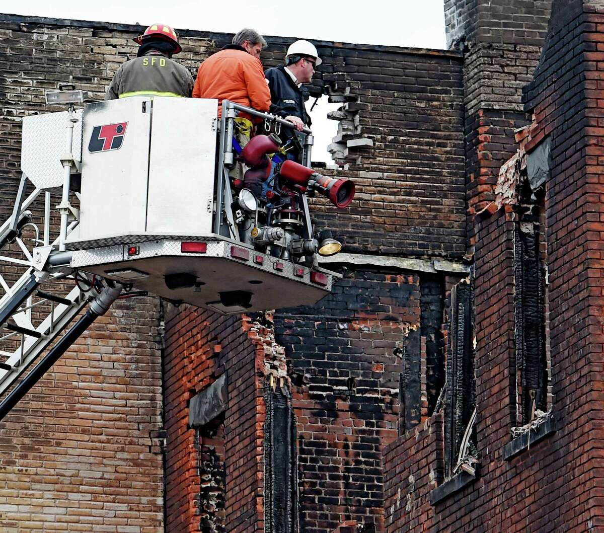 City Building Inspector Eric Schilling, right points toward 104 Jay Street Monday afternoon March 16, 2015, as the investigation continues as to the cause and origin of the fire that took four lives in Schenectady, N.Y. (Skip Dickstein/Times Union)