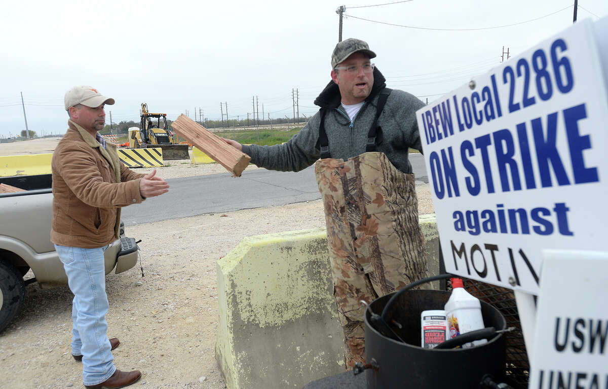 Jason Beuhler hands off firewood to fellow Motiva striker Scott Danks during a stop at the main gate strike station for heating supplies as the strike continues at the Motiva plant in Port Arthur Monday. Members of the local IBEW and ISW unions began their strike at midnight February 21 after failing to come to an agreement with the company on their contract renewal. At issue are two key components, successorship and retrogression. Workers say they have been receiving support from the community, who have stopped by to donate food and beverages to the picketing workers, as well as retired union workers who experienced past strikes. Photo taken Monday, February 23, 2015 Kim Brent/The Enterprise