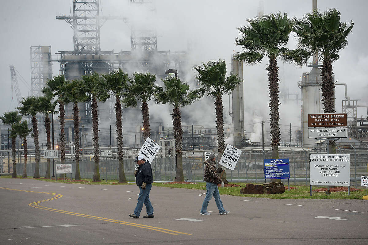 Picketers walk the line outside the main gate as the strike continues at the Motiva plant in Port Arthur Monday. Members of the local IBEW and ISW unions began their strike at midnight February 21 after failing to come to an agreement with the company on their contract renewal. At issue are two key components, successorship and retrogression. Workers say they have been receiving support from the community, who have stopped by to donate food and beverages to the picketing workers, as well as retired union workers who experienced past strikes. Photo taken Monday, February 23, 2015 Kim Brent/The Enterprise