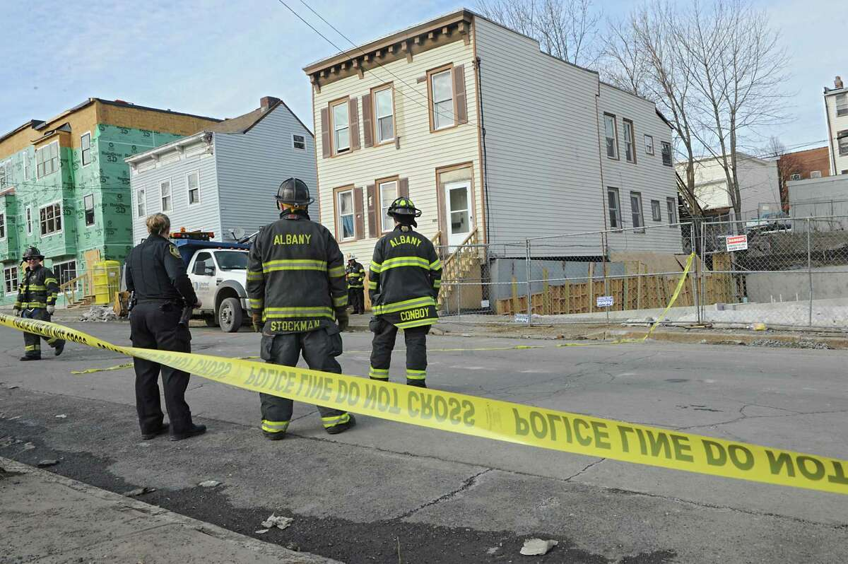 Police and firefighters stand outside a home at 211 Sheridan Ave. on Friday, March 13, 2015 in Albany, N.Y. The building partially collapsed during construction for the excavation site for a 12-unit apartment building. The home is just down the street from new Habitat for Humanity homes being built. (Lori Van Buren / Times Union) ORG XMIT: MER2015031317042604