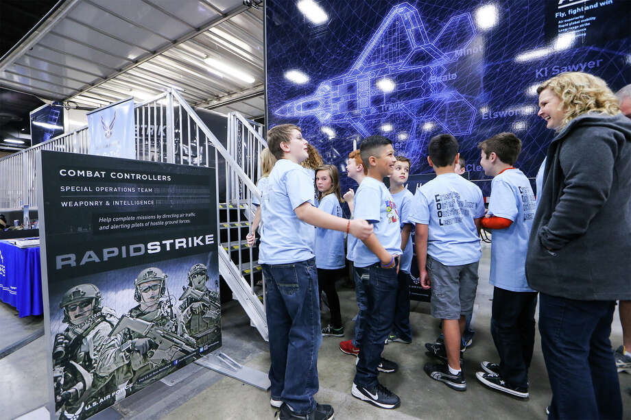 "Members of the ""Beastmode Builders"" robotics team from Watts Elementary in Cibolo wait in line to experience the Air Force Recruiting Service's ""Rapid Strike"" simulator, displayed during the FIRST Alamo Regional competition at the Convention Center on Saturday, March 14, 2015. Rapid Strike is a full-motion simulator ride that gives visitors a look at an F-22 flight, a C-17 cargo drop and illustrates Special Operations ground surveillance, satellite communications and a Reaper missile strike — all from a first-person point of view in a six-munute ride. Photo: Marvin Pfeiffer /San Antonio Express-News / Express-News 2015"