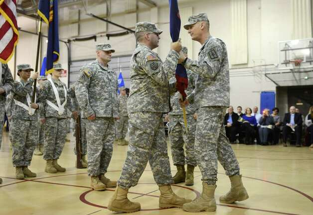 New York Army National Guard Lt. Col. James Gonyo, left,  is handed the New York Army National Guard Recruiting and Retention Battalion colors by Major General Patrick Murphy, the Adjutant General, after taking command of the battalion during a ceremony Monday, March 16, 2015, at the State Division of Military and Naval Affairs headquarters in Colonie, N.Y. Lt. Col. Gonyo replaced Lt. Col. Henry Pettit. (Will Waldron/Times Union) Photo: WW / 00031045A