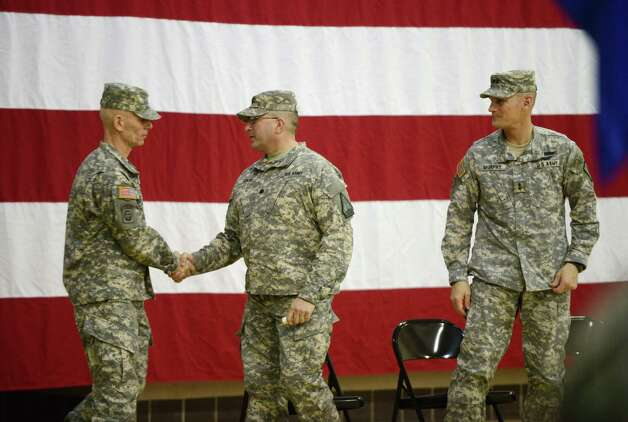 Outgoing New York Army National Guard Recruiting and Retention Battalion commander, Lt. Col. Henry Pettit, left, shakes the hand of his successor Lt. Col. James Gonyo, center, during a change of command ceremony Monday, March 16, 2015, at the State Division of Military and Naval Affairs headquarters in Colonie, N.Y. Major General Patrick Murphy, the New York Army National Guard Adjutant General, right, observes the handshake. (Will Waldron/Times Union) Photo: WW / 00031045A