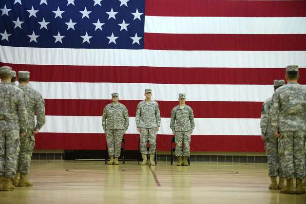 New York Army National Guard Lt. Col. James Gonyo, left, Lt. Col. Henry Pettit, center, and Major General Patrick Murphy, the New York Army National Guard Adjutant General, right, stand at attention during the conclusion a change of command ceremony Monday, March 16, 2015, at the State Division of Military and Naval Affairs headquarters in Colonie, N.Y.  Lt. Col. Gonyo took command of the New York Army National Guard Recruiting and Retention Battalion from Lt. Col. Henry Pettit. (Will Waldron/Times Union) Photo: WW / 00031045A