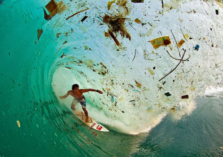 Surfer Dede Surinaya catches a wave in a remote but garbage-covered bay on Java, Indonesia, the world's most populated island. Photo: © Zak Noyle