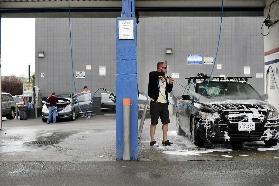 Travis Coffman of Oakland uses a high pressure spray gun to rinse off the soap as he washes his car at the Golden Coin Car Wash in Oakland, CA, on Monday, March 16, 2015. Monday, one day before state officials consider expanding water restrictions for homes and businesses as California deals with a fourth straight year of drought. The new mandates could limit Californians to watering their lawns just two days a week, while restaurants and bars would be prevented from serving water without a customer request and hotels would have to get approval from guests before washing their towels and sheets. Commercial car washes traditionally tap less water than do-it-yourself driveway washers, by using high-pressure hoses and recycling a portion of the water that otherwise would end up in the street and storm drains. California's rainy season, which is coming to a close, is on track to be the fourth in a row with below-average precipitation. The state's largest reservoirs are lower than normal, while the snowpack that recharges the reservoirs is less than a fifth of average. Photo: Michael Short