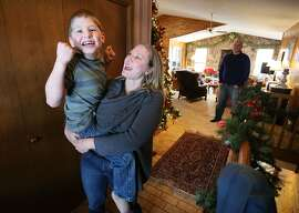 In this Jan. 1, 2015, photo, Nicole Gross plays with her son Chase, who is autistic and epileptic, at their home in Colorado Springs, Colo. Chase was moved from Chicago to Colorado so he could legally access a medical marijuana oil known as Charlotte's Web. (AP Photo/Brennan Linsley)