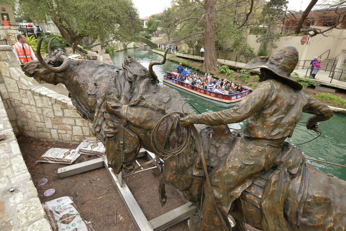 Riverwalk visitors look at the 3 ton T.D. Kelsey sculpture, Coming Home to the Briscoe, depicting a vaquero driving longhorns on a cattle drive. The work was installed Monday afternoon along the Riverwalk entrance to the Briscoe Western Art Museum.