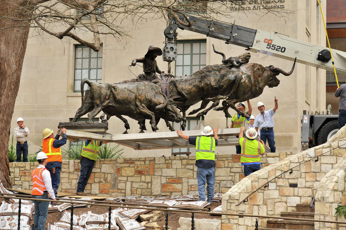 Workers lower the 3 ton bronze sculpture,