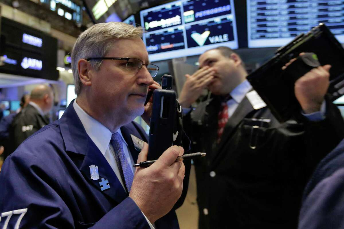 Trader Christopher Fuchs, left, works on the floor of the New York Stock Exchange, Monday, March 16, 2015. U.S. stocks opened higher, led by health care and utilities companies, rebounding after three weeks of losses. (AP Photo/Richard Drew) ORG XMIT: NYRD101