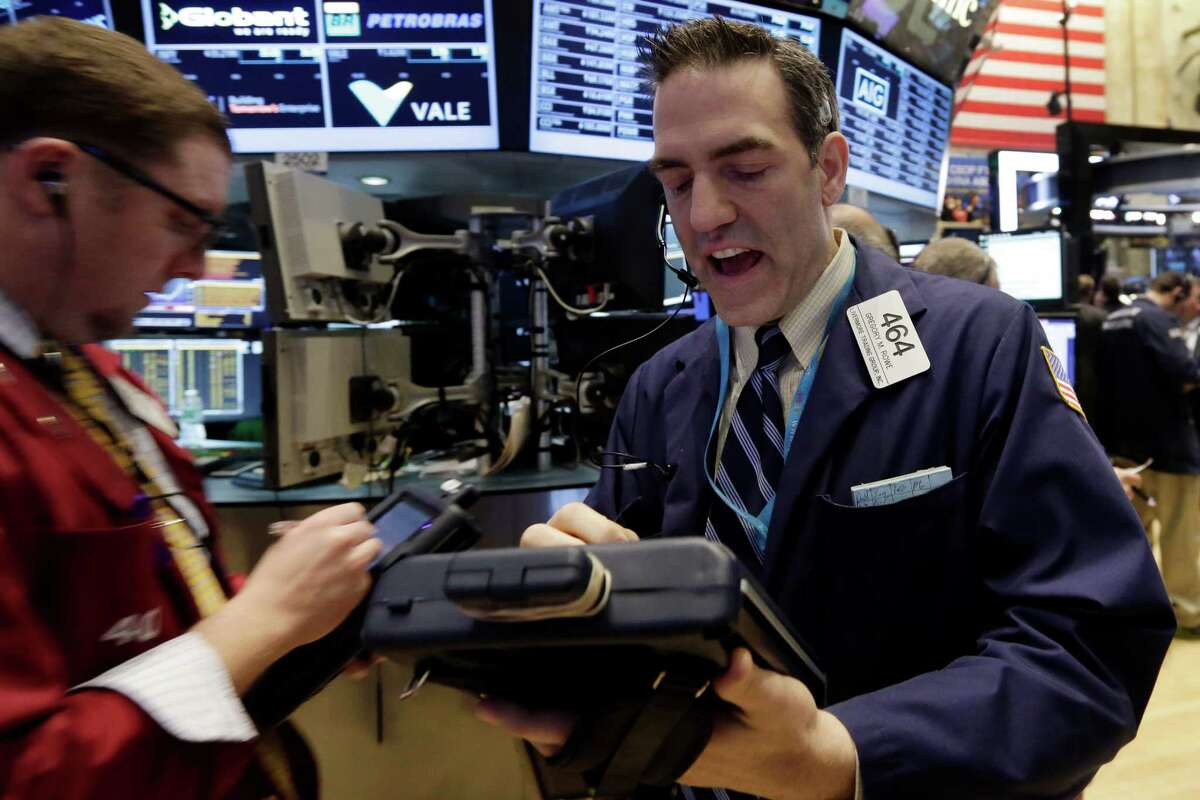 Trader Gregory Rowe, right, works on the floor of the New York Stock Exchange, Monday, March 16, 2015. U.S. stocks opened higher, led by health care and utilities companies, rebounding after three weeks of losses. (AP Photo/Richard Drew) ORG XMIT: NYRD102