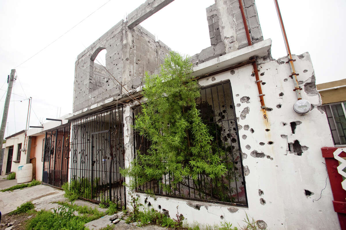 This house at Aruba Street and Matte R. Gomez Street in Matamoros, Mexico, is riddled with bullet holes after a gun fight.