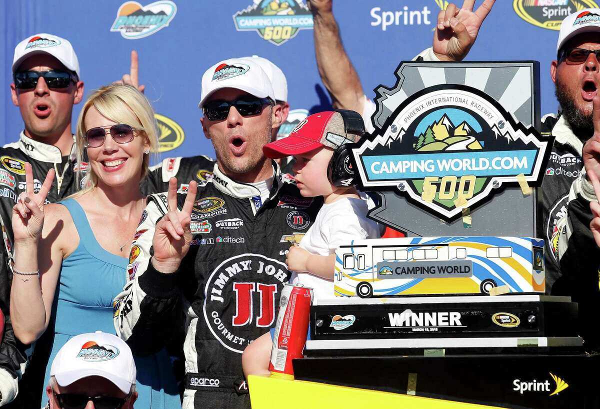 Kevin Harvick poses with his wife DeLana, left, and son Keelan, after winning a NASCAR Sprint Cup Series auto race on Sunday, March 15, 2015, in Avondale, Ariz. (AP Photo/Rick Scuteri) ORG XMIT: AZRS114