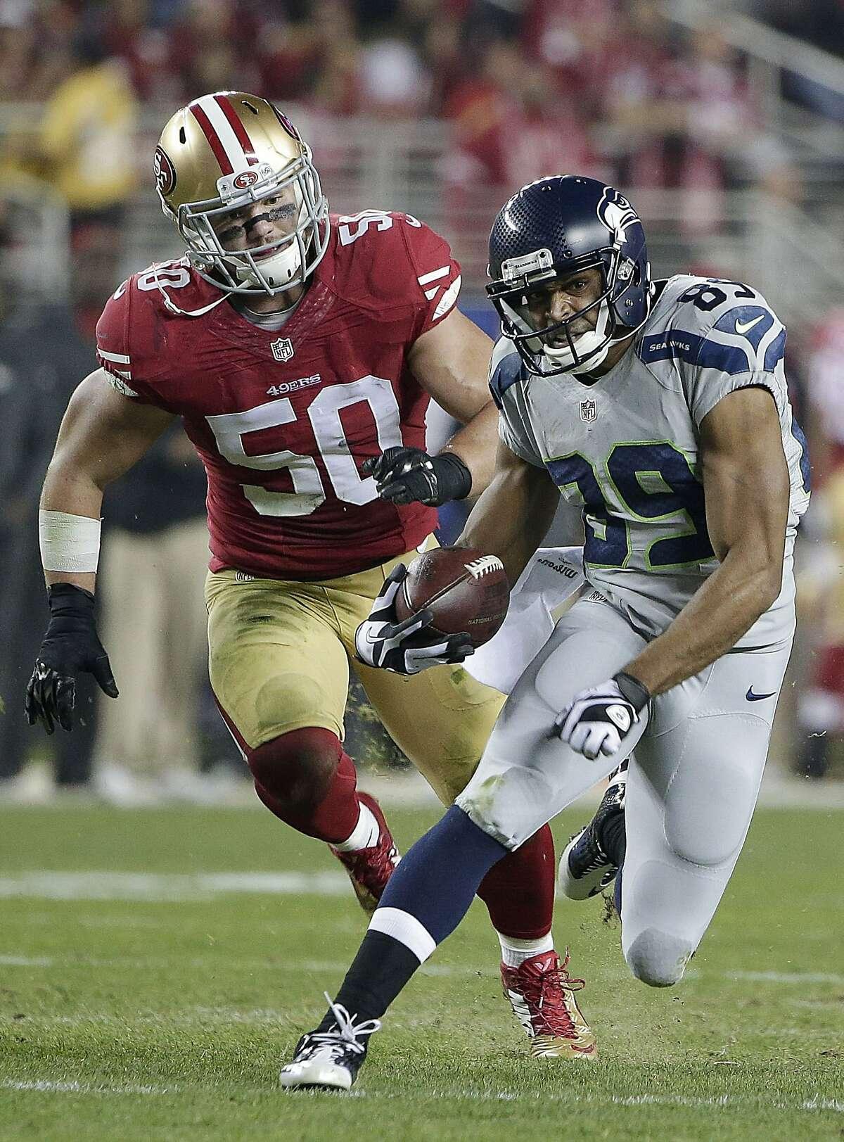 Seattle Seahawks wide receiver Doug Baldwin (89) runs from San Francisco 49ers inside linebacker Chris Borland (50) during the first quarter of an NFL football game in Santa Clara, Calif., Thursday, Nov. 27, 2014. (AP Photo/Marcio Jose Sanchez)