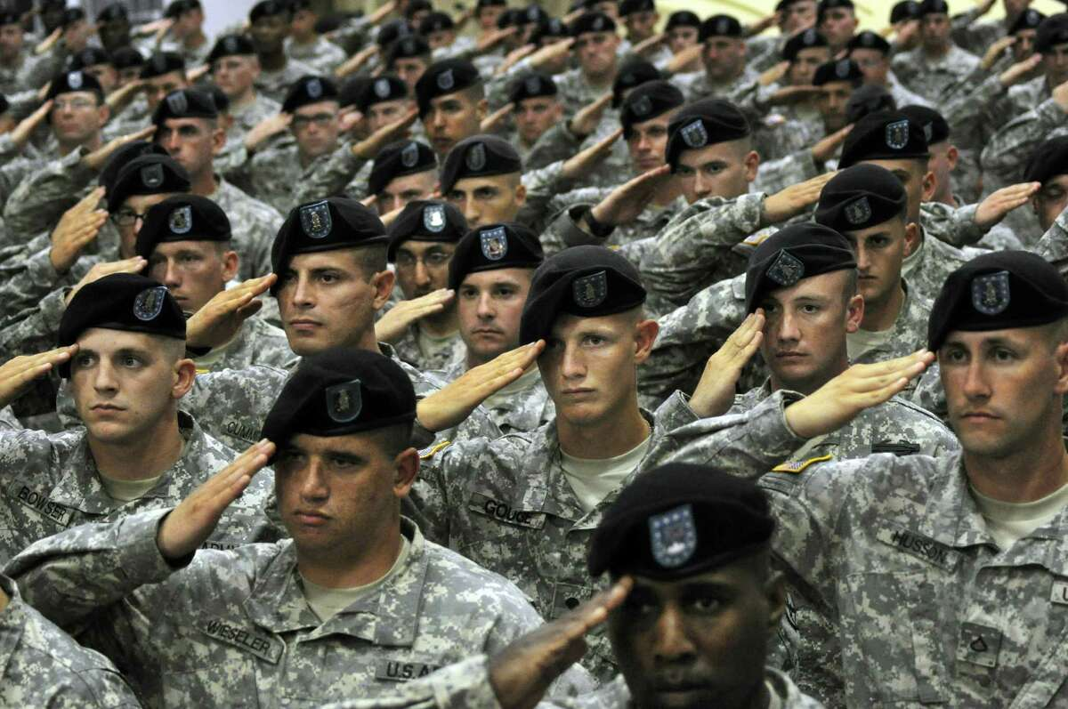FILE - This July 28, 2010 file photo shows soldiers from the 10th Mountain Division saluting during the National Anthem during a welcome home ceremony attended by Vice President Joe Biden in Fort Drum, N.Y. In a massive restructuring, the U.S. Army is slashing the number of active duty combat brigades from 45 to 33, and shifting thousands of soldiers out of bases around the country as it moves forward with a longtime plan to cut the size of the service by 80,000. The U.S. Army plans to eliminate one of three combat brigades at northern New York's Fort Drum. (AP Photo/Heather Ainsworth, File) ORG XMIT: WX107