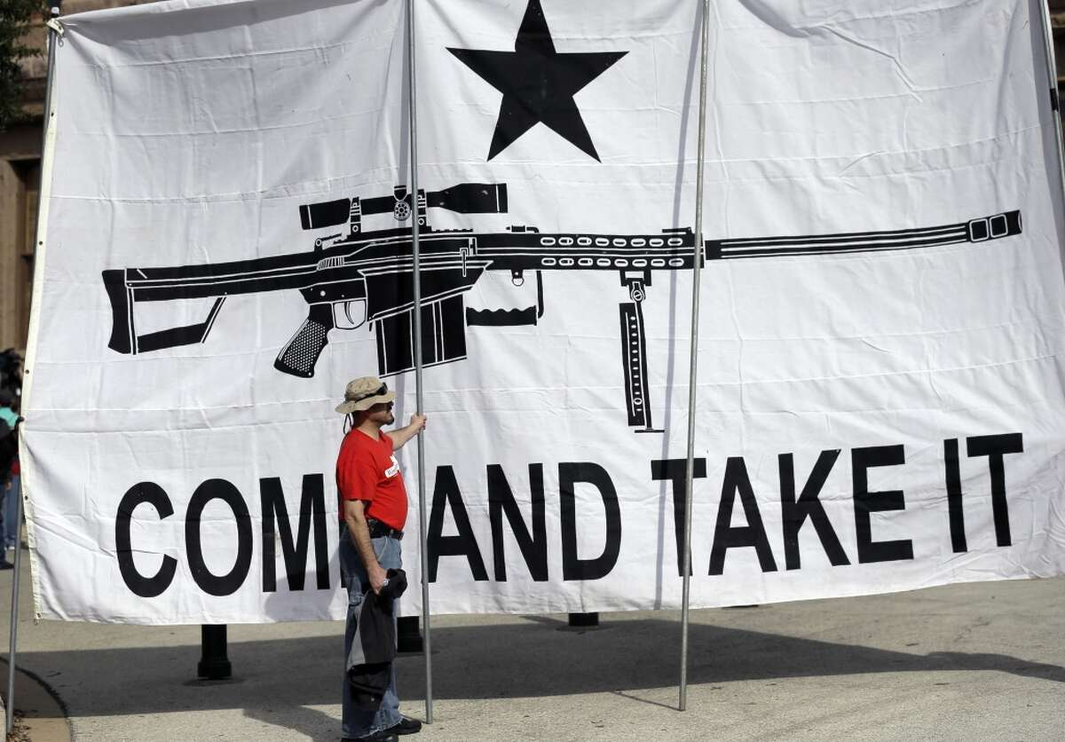 """A demonstrator helps hold a large """"Come and Take It"""" banner at a rally in support of open carry gun laws at the Capitol, Monday, Jan. 26, 2015, in Austin, Texas. (AP Photo/Eric Gay)"""