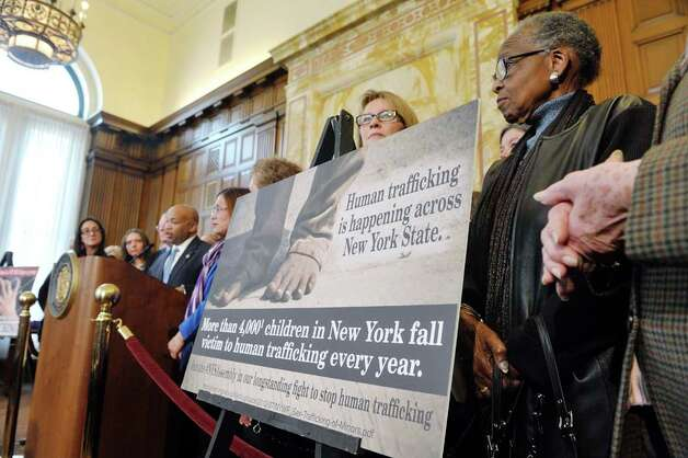 Assembly Speaker Carl Heastie, background at podium, members of the Assembly Majority, survivors of sex trafficking and advocates for the survivors take part in a press conference to discuss human trafficking legislation on Monday, March 16, 2015, at the Capitol in Albany, N.Y.  (Paul Buckowski / Times Union) Photo: PAUL BUCKOWSKI, Albany Times Union / 00031049A