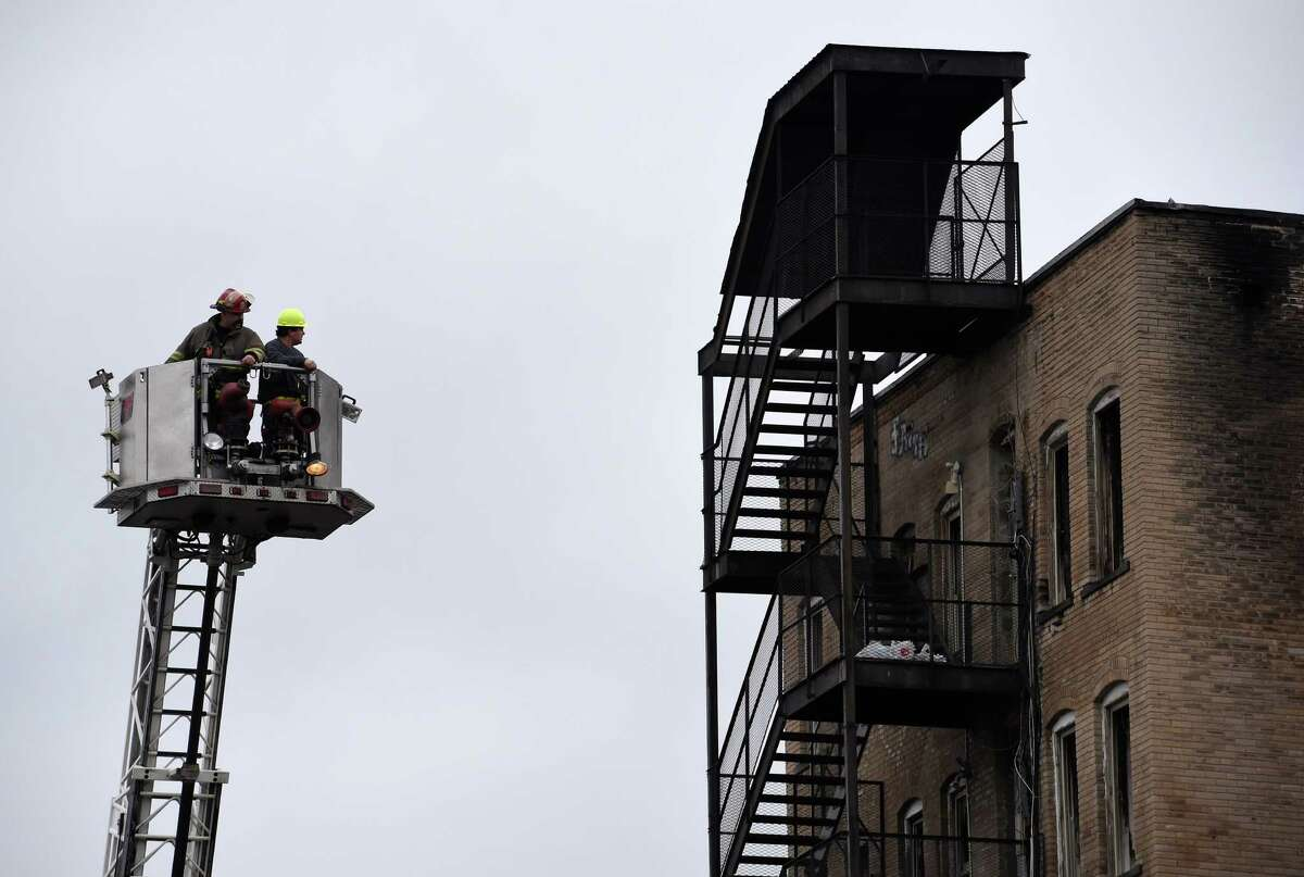 A demolition contractor is taken aloft behind the burned out hulks of 100-102 and 104 Jay Street Tuesday morning March 17, 2015 in Schenectady, N.Y., to do an inspection of the site for bidding purposes. (Skip Dickstein/Times Union)
