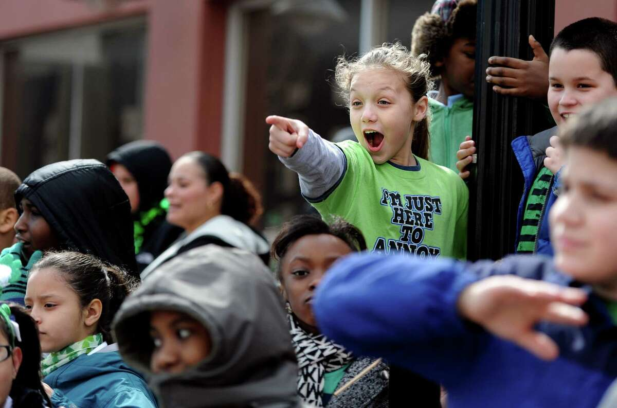 Ten-year-old Tieno Cotto, points to The Cycling Murrays as they pass her and her classmates from Hall School on their mix of bikes and unicycles on Main Street in Bridgeport Tuesday, Mar. 17, 2015 during the 33rd Annual St. Patrick's Day Parade