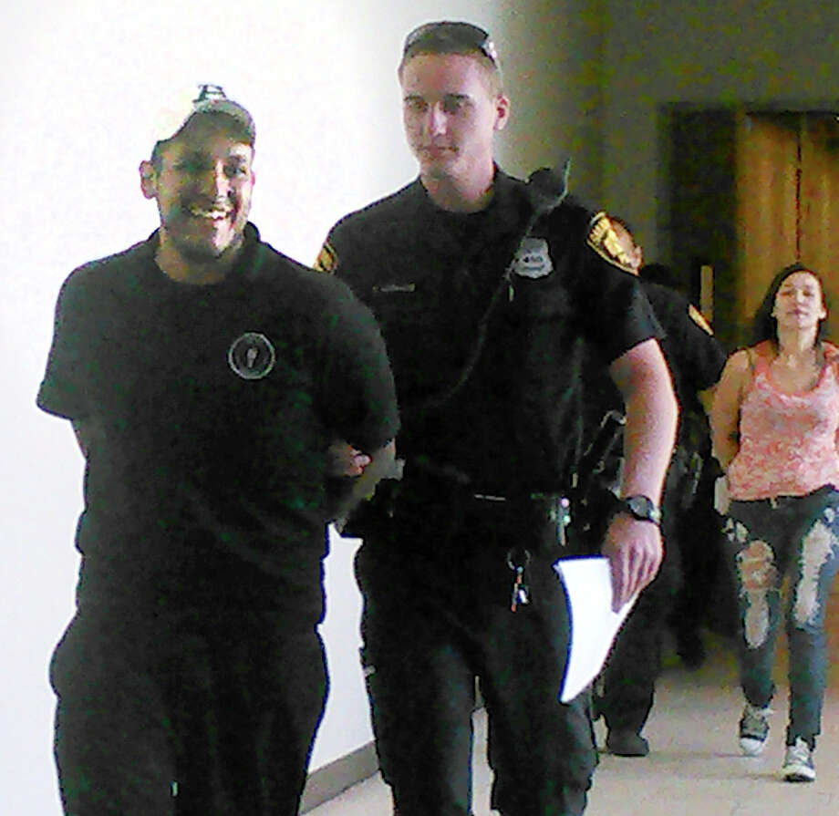 Joe Martinez, 24, left, was arrested April 4 on a warrant for the 2010 killing of David Valdez. His then-girlfriend, in background, Rebecca Rodriguez, 23, was also arrested on a charge of felony theft. Photo: Mark D. Wilson /San Antonio Express-News / © 2014 San Antonio Express-News