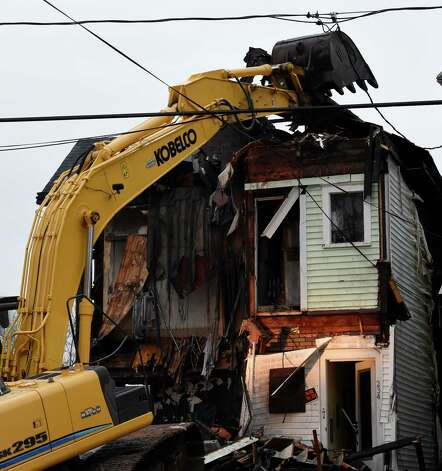 Demolition begins on the home at 234 Delaware Avenue Tuesday morning March 17, 2015 after a fire destroyed the structure last evening in Albany, N.Y.  Three firefighters were injured fighting the blaze that left 11 homeless.     (Skip Dickstein/Times Union) Photo: SKIP DICKSTEIN