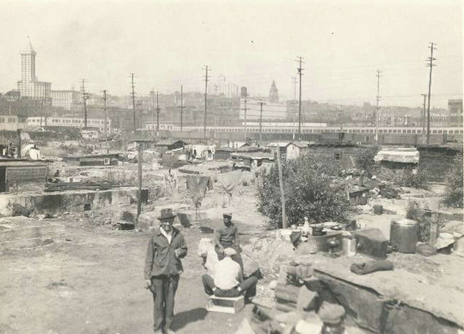 Pictured on July 20, 1932, this Hooverville is a much earlier variation on the homeless encampments we see across Seattle today. This camp was in the Eddy and Skinner Shipyard in Sodo, located west of the end of South Atlantic Street. The Smith Tower and King Street Station clock tower are visible and remain in place today, though they are much harder to see from that location. Photo: Seattle Municipal Archive