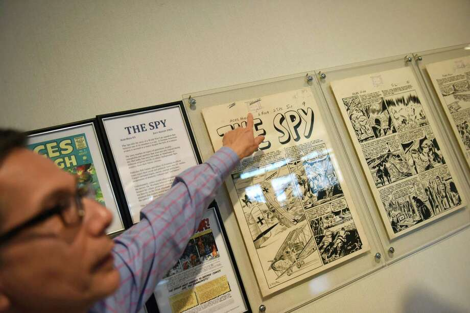 """Greenwich resident Robert Reiner shows original drawings of the story """"The Spy"""" from the comic book """"Aces High"""" at the exhibit """"KA-POW! When Comics Imperiled America"""" at the Greenwich Library Flinn Gallery in Greenwich, Conn. Tuesday, March 17, 2015.  Original full-size pen-and-ink drawings of 10 Entertaining Comics (EC) complete stories from 1950-1955 are on display.  KA-POW! is the first exhibit of EC comic book art that focuses on the censorship of the 1950s. Photo: Tyler Sizemore / Greenwich Time"""