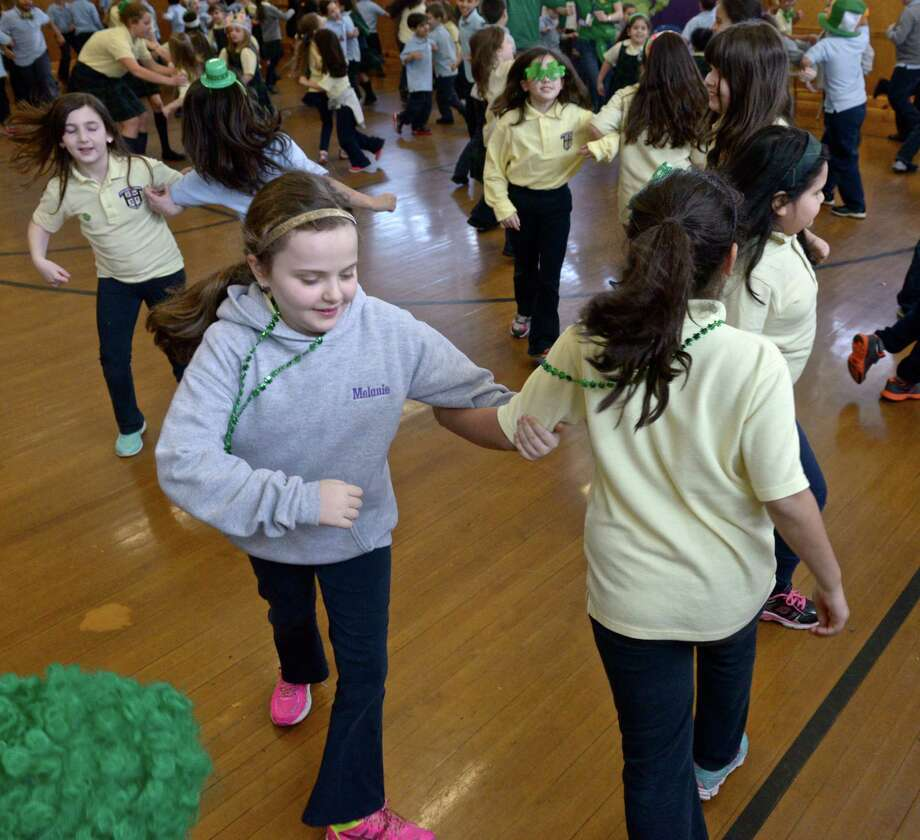 Melanie Riggs, left, and Isabella de Souza, third grade class mates, dance to Irish music during a St Patrick's Day assembly at Saint Joseph's School on Tuesday, March 17, 2015, in Danbury, Conn. Photo: H John Voorhees III / The News-Times