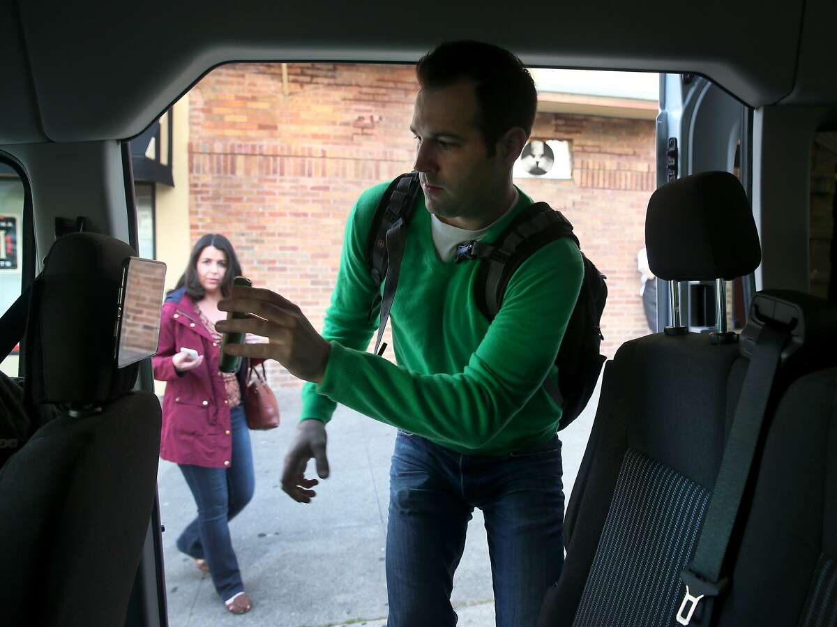 """Steve Uphaus scans his phone to pay the fare while he enters a """"Chestnut Express"""" Chariot commuter van as Emma McGurk (left) waits to board in San Francisco, Calif. on Tuesday, March 17, 2015."""