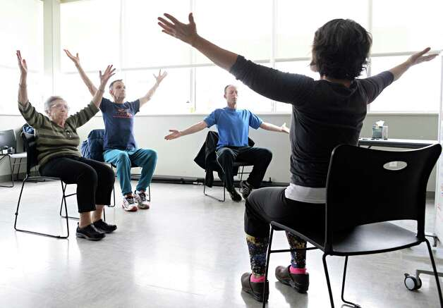Instructor Tamara Rossiter, right, conducts a Yoga for Parkinson's class with students, from left, Loretta Brogna of Niskayuna, Tom Stephany of Delmar and Bruce Plotsky of Clarksville at Honest Weight Food Co-op's community room Thursday March 5, 2015 in Albany, NY.  (John Carl D'Annibale / Times Union) Photo: John Carl D'Annibale / 10030886A