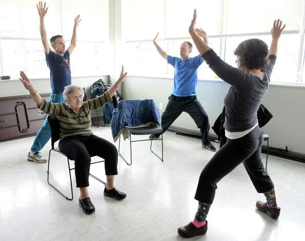 Instructor Tamara Rossiter, right, conducts a Yoga for Parkinson's class with students, from left, Tom Stephany of Delmar, Loretta Brogna of Niskayuna and Bruce Plotsky of Clarksville at Honest Weight Food Co-op's community room Thursday March 5, 2015 in Albany, NY.  (John Carl D'Annibale / Times Union) Photo: John Carl D'Annibale / 10030886A