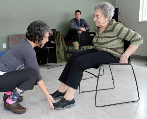 Instructor Tamara Rossiter, left, works with Loretta Brogna of Niskayuna during a Yoga for Parkinson's class at Honest Weight Food Co-op's community room Thursday March 5, 2015 in Albany, NY.  (John Carl D'Annibale / Times Union) Photo: John Carl D'Annibale / 10030886A