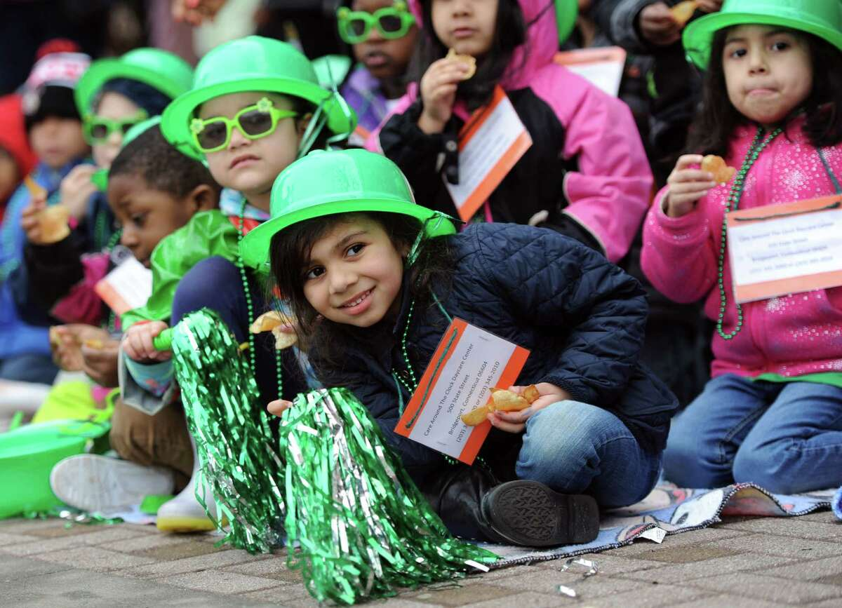 Four-year-old Stella Mesquita leans forward to see the marchers as she watches the 33rd Annual St. Patrick's Day Parade with her friends from Care Around the Clock Daycare as it moves down Broad Street in Bridgeport Tuesday, Mar. 17, 2015.