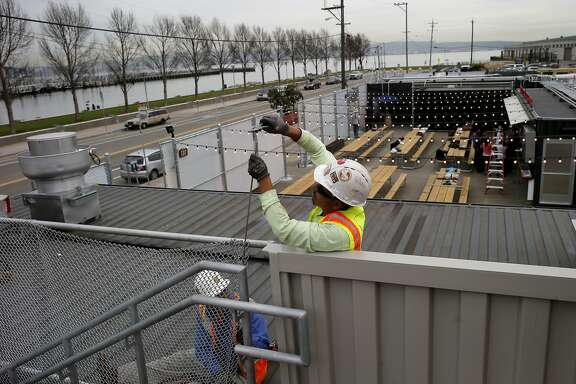 Workers complete a cyclone fence to keep visitors off the roof of one container Monday March 16, 2015. The Giants' Yard at Mission Rock bills itself as a pop-up shipping container village that has local food and drink, public space and events. It joins other shipping container stores like Proxy at Octavia and Hayes Streets in San Francisco, Calif.