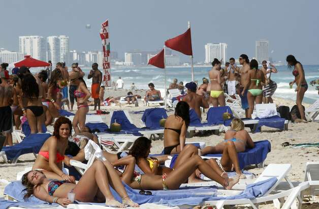 In this March 10, 2012 photo, people hang out on the beach during spring break in Cancun, Mexico. The beach resort remains a top destination for American spring-breakers seeking an escape from winter. Photo: Israel Leal, Associated Press