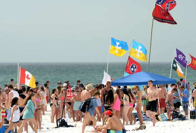 Flags fly over a crowd of spring breakers on the beach near the Whale's Tail Beach Bar & Grill in South Walton County near Destin, Fla., on Monday, March 9, 2015.  Photo: Devon Ravine, Associated Press
