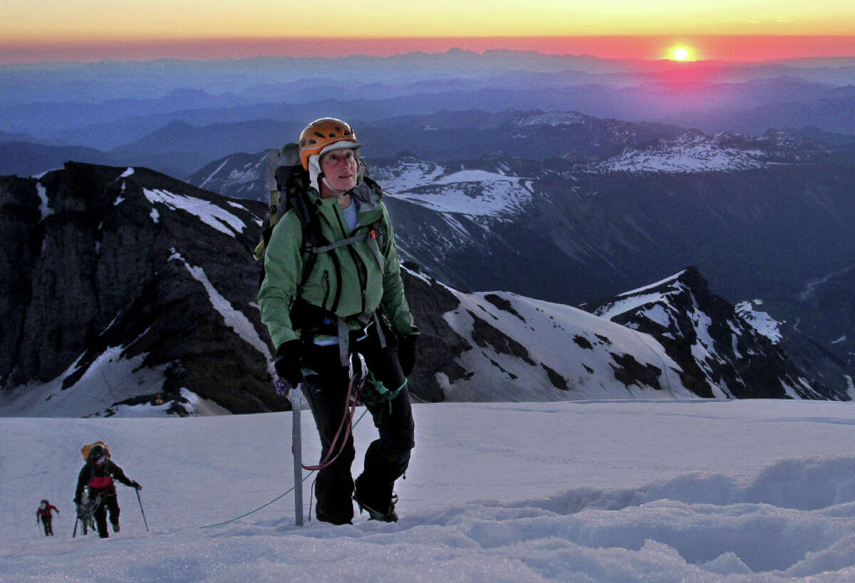 In a July 9, 2010 photo, Sally Jewell, CEO of REI, leads a five-woman team up the Emmons Glacier and ultimately to the top of Mount Rainier as the sun rises. A little more than one year later, President Obama picked Jewell to lead the Interior Department.  She is now sharply critical of the Trump administration wanting to charge a $70 entrance fee to Mount Rainier National Park.