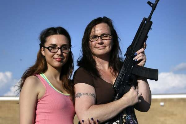 Tara Cowan, right, of Euless, Texas, and her daughter Selena Canela, left, members of Open Carry Tarrant County, pose for a portrait with a Saiga 556 rifle as they and other members of the group Open Carry Tarrant County gathered for a demonstration, Thursday, May 29, 2014, in Haltom City, Texas. North Texas gun rights advocates are suing the city of Arlington for amending an ordinance that they claim is discriminatory and infringes upon free speech rights, in the latest sign of growing tensions among gun activists and government forces in Texas. (AP Photo/Tony Gutierrez)