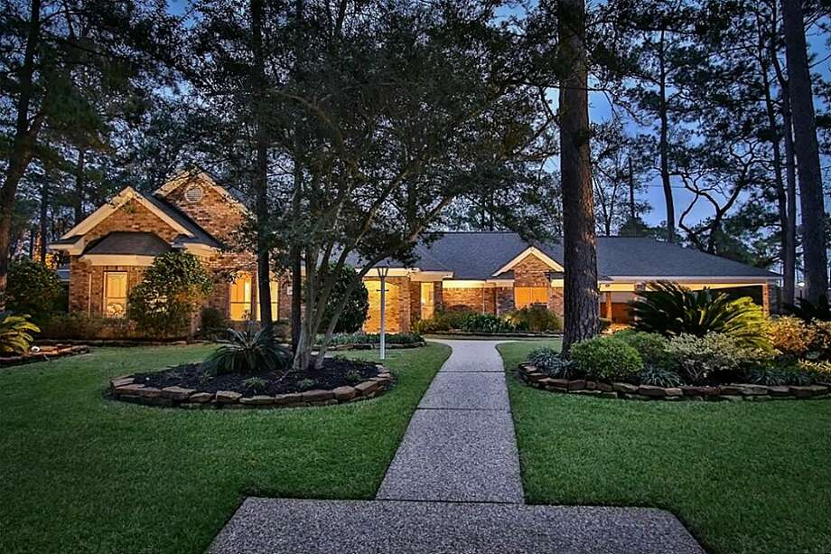 Tomball: Three-bedroom home has wood floors downstairs, a covered patio and a laundry room with wine storage. Garage has been converted to a home gym/media room. 3,132 square feet Photo: HAR