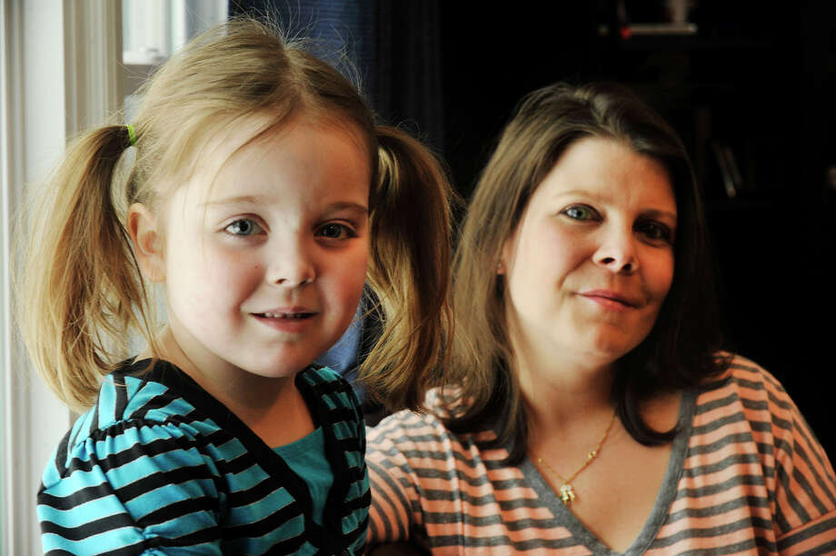Five-year-old Ella Wright and her mother, Dana Haddox-Wright, pose for a photograph at their home in Wilton, Conn., on Tuesday, March 17, 2015. Ella has Dravet syndrome, a form of childhood epilepsy. Dana is an advocate for medical marijuana use. Even though her daughter's syndrome is on the mild side, Dana has seen cases in Colorado, where marijuana is legal, that have drastically reduced or stopped the the seizures. She says she wants to see medical marijuana available for research on the proper dosage and effectiveness in children especially for use on children who suffer from more aggressive forms of the syndrome as a last resort once all other avenues have been exhausted. Photo: Jason Rearick / Stamford Advocate