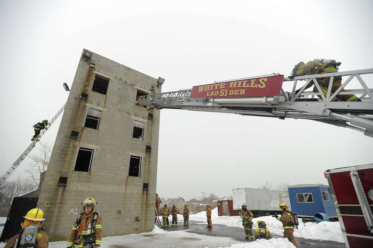 """Student volunteer firefighters representing ten towns practice a drill called """"the anthill"""", ascending and descending ladders from a structure, during the Valley Fire Chiefs Regional Training School's Firefighter 1 class at the Fairfield Regional Fire School facility in Fairfield, Conn. on Sunday, March 1, 2015."""