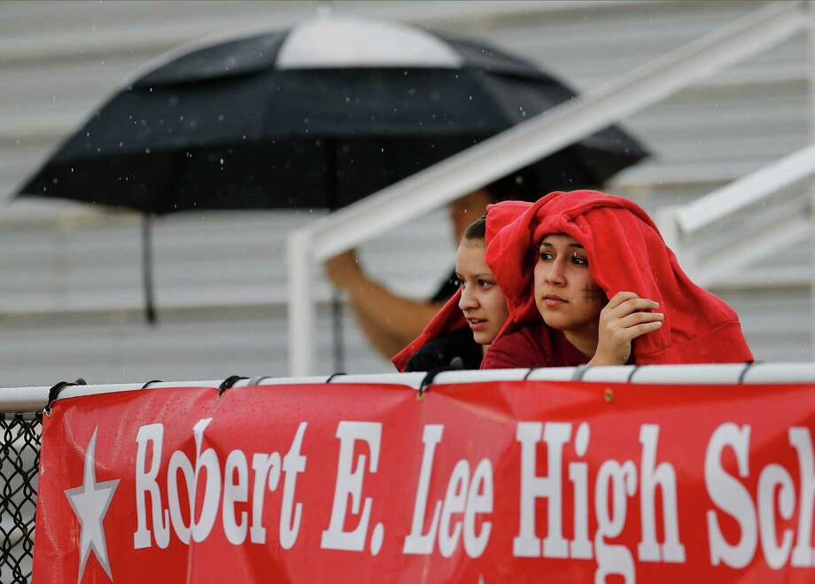 Marissa Regino (right) and Katie Jimenez cheer on their friend playing in a soccer match between Lee High School and Reagan High School during a rain shower at Comalander Stadium on Tuesday, Mar. 17, 2015. Photo: Kin Man Hui, San Antonio Express-News / ©2015 San Antonio Express-News