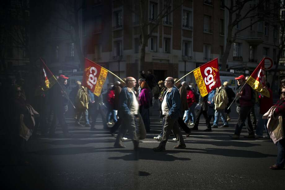 A man holds a CGT union flag as he participates in a demonstration in Paris on March 17, 2015 calling for the protection of the rights of retirees. Thousands of people participated in marches called by various trade unions across France calling for greater protection for the rights of retirees. Photo: Martin Bureau, AFP / Getty Images