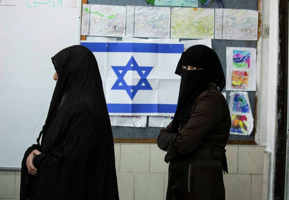 Bedouin women wait to cast their votes at a polling station in the town of Rahat, Tuesday, Mar. 17, 2015. Israelis are voting in early parliament elections following a campaign focused on economic issues such as the high cost of living, rather than fears of a nuclear Iran or the Israeli-Arab conflict. (AP Photo/Tsafrir Abayov) ORG XMIT: DV124 Photo: Tsafrir Abayov / AP