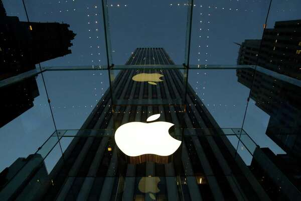 FILE - In this Wednesday, Nov. 20, 2013, file photo, the Apple logo is illuminated in the entrance to the Fifth Avenue Apple store, in New York. Apple's widely used iTunes and app stores suffered a rare breakdown Wednesday, March 11, 2015, frustrating millions of music lovers and mobile device owners around the world. (AP Photo/Mark Lennihan, File)